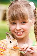 happy girl feed rabbit with carrot. - stock photo