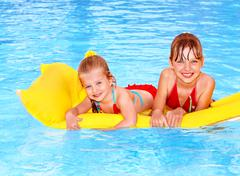 kids swimming on inflatable beach mattress. - stock photo