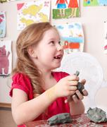 Child moulding from clay in play room. Stock Photos