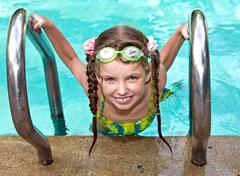 Girl in protective goggles leaves pool. Stock Photos
