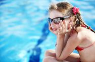 Child girl in red bikini and glasses near  swimming pool. Stock Photos