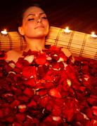 Beautiful girl in jacuzzi with rose petal and candle. Stock Photos