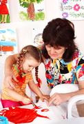 child with teacher draw paints in playroom. - stock photo