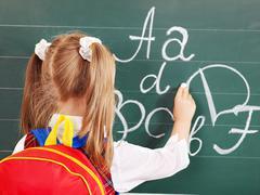 schoolchild writting on blackboard - stock photo