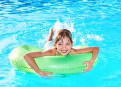 kid on inflatable ring in swimming pool. - stock photo