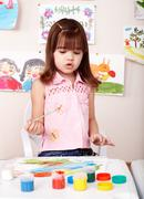 child paint picture in preschool. - stock photo