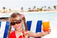 Child girl in sunglasses and red bikini drink  juice. Stock Photos