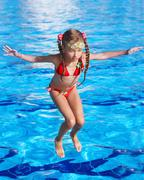 girl with  goggles and red swimsuit jump in swimming pool. - stock photo