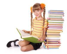 Schoolgirl reading pile of books. Stock Photos