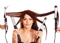 Woman holding iron curling hair. Stock Photos