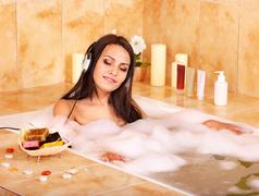 Woman listening to music in bath Stock Photos