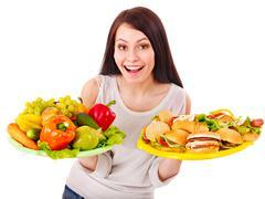 woman choosing between fruit and hamburger. - stock photo