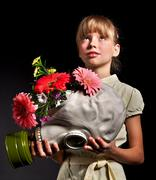 child holding flowers and gas mask . - stock photo