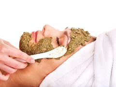 Woman getting facial mask in spa . Stock Photos
