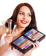 girl holding eyeshadow and makeup brush. - stock photo