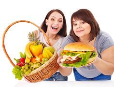 women choosing between fruit and hamburger. - stock photo
