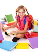 Happy sitting schoolgirl in eyeglasses  with  pile of books. Stock Photos