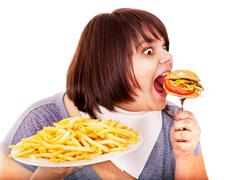 overweight woman eating hamburger. - stock photo