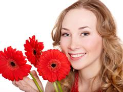 Stock Photo of happy young woman holding flowers.