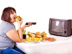 Woman eating fast food and watching tv. Stock Photos