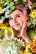Beautiful girl with butterfly and flower on grass. Stock Photos