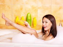 Woman wash leg in bathtube. Stock Photos