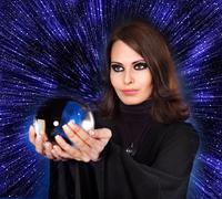girl with fortune telling ball against  star sky. - stock photo