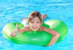child sitting on inflatable ring thumb up. - stock photo