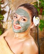 woman having clay facial mask apply by beautician. - stock photo