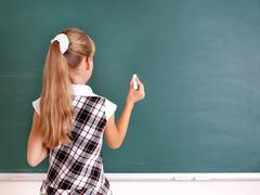 schoolchild writing on blackboard. - stock photo
