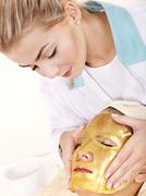 Woman with gold facial mask. - stock photo