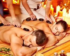 Woman and man getting stone therapy massage in spa. Stock Photos