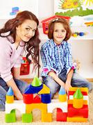 family with child playing bricks. - stock photo