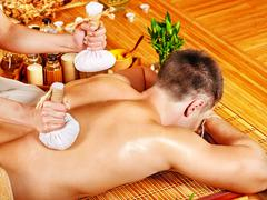 Stock Photo of man getting herbal ball massage treatments .