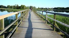 Grey head man drive bicicle wooden long bridge lake Stock Footage