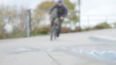 BMX rider skids bike into ramp - stock footage