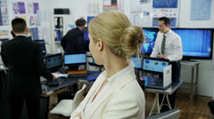 Portrait of a successful financial trader with her colleagues in the background. Stock Footage