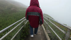 Man walks down Point Reyes Lighthouse steps in mist and fog HD 1025 Stock Footage