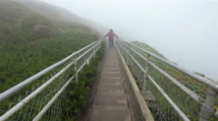 Man walks up steep Point Reyes Lighthouse steps in rain mist and fog HD 1025. Stock Footage