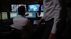 Security personnel watching the screens in a dark system control room - stock footage
