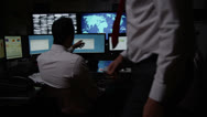 Stock Video Footage of Security personnel watching the screens in a dark system control room