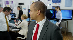 Portrait of a successful financial trader with his colleagues in the background. Stock Footage