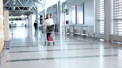 Young woman pulling luggage hand-cart with bags - stock footage
