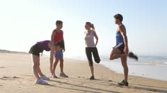 Four People Warming Up Before Exercising On Beach Stock Footage
