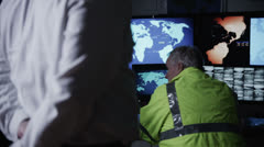Security personnel watching the screens in a dark system control room Stock Footage