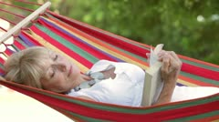 Senior Woman Relaxing In Hammock With Book Stock Footage