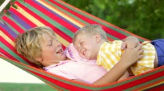 Two Boys Relaxing In Garden Hammock Together Stock Footage