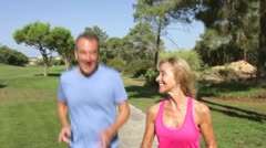 Senior Couple Jogging In Park - stock footage