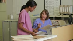 Doctor In Discussion With Nurse At Nurses Station - stock footage