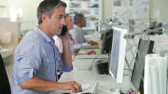 Man Office At Desk Using Mobile Phone And Computer Stock Footage